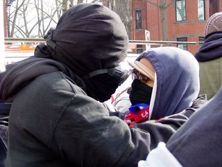 Two black bloc demonstrators share an intimate moment along the march route while we were stopped briefly.