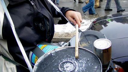 A person carrying a set of makeshift drums makes a beat for the marchers.