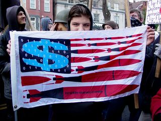 This person holds up a flag showing a twist on the United States flag showing what is perceived as the real truth behind the war on terror. The flag also advertises truth-now.com.