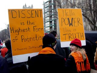 As one sign reminds us what patriotism really is, the other speaks truth to power.