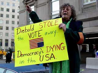 This woman, standing on her car, shows a poster criticizing Diebold, a manufacturer of election equipment.