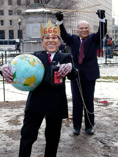 """In another instance, two people dressed like George W. Bush and Dick Cheney. The man in the Bush mask wore a gold crown saying """"666"""", held an inflatable globe and a bottle of motor oil, and had strings attached to his arms. The strings were to make Bush look like a puppet, and they were held by another man wearing a Dick Cheney mask."""