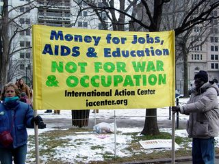 Banners held at the edges of McPherson Square advertise the next big demonstration, and also take a stand on spending.