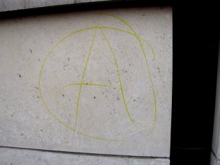Anarchy sign drawn on the IFC building. At the time, I believed this to be a chalk marking, but upon later examination of the photo, this was probably ink.