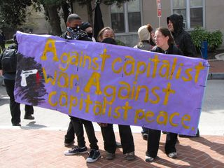 Holding one of the banners on a section of sidewalk to the west of Washington Circle.