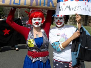 Two women dressed in clown makeup, advocating art and education over war.