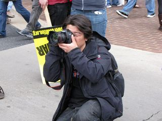 A photographer takes a moment to shoot a photo of the assembled crowd.