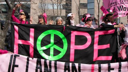 Code Pink demonstrators hold up multiple banners.