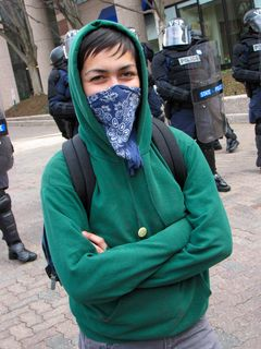 A masked demonstrator poses for a photo in front of the cops.