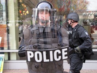 Meanwhile, the Virginia State Police (above) and local police (below), in full riot gear, formed a line preventing movement towards the buildings. And despite my best attempts to get some of them to smile, they maintained their poker faces.