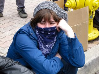 A masked demonstrator sits on the sidewalk. The mask hides much of her expression, but one has to wonder what she's thinking about in these photos...
