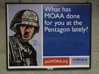 Metro advertisement for the Military Officers Association of America at Crystal City station, after anti-war protesters had their way with it.