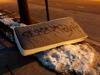 """I spotted this on the side of 14th Street NW on February 28. """"Sleep tight"""" is written on the mattress in spray paint. Kind of creepy, no?"""
