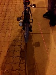 I spotted this on Georgia Avenue on the evening of April 16. This is a bike-mounted laser that projects two lines onto the sidewalk, delineating a keep-out zone on either side of the bicycle.