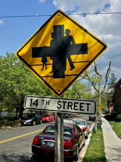 This sign, photographed May 2, on the 1400 block of Aspen Street NW in DC, consists of two different legends printed over each other: the intersection sign over top of the family version of pedestrian crossing. Regarding this juxtaposition, I commented at the time that this must mean that we can run people over at this intersection.