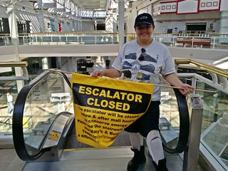 """Elyse poses for a photo with the """"Escalator Closed"""" sign."""