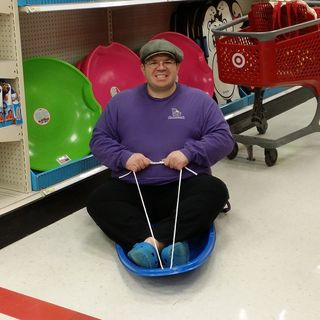 Pretending to go sledding in Target. We used to have one just like this when I was a child, but in orange.
