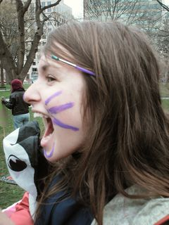 Face painting, with a peace sign on one side, and catlike features on the other.