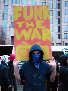 """A masked individual holds a hand-painted """"Funk the War"""" sign."""