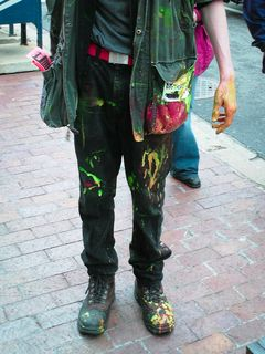 A demonstrator stands covered in paint following the breaking of several paint bombs.