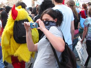 Handing off the camera to a masked demonstrator, and then... taking a picture!
