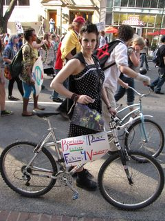 """A woman's bicycle carries a sign with the classic phrase, """"Bombing for peace is like f---ing for virginity""""."""
