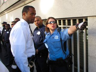 An MPDC officer explains to a Secret Service officer about how the people got up on the ledge.