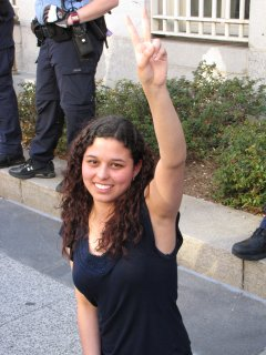 A woman gives the peace sign for the camera.