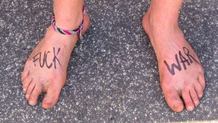 A simple, if slightly uncouth, anti-war message written on a pair of feet.