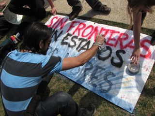 """Making our large out-in-front banner. Translated, the banner reads, """"Without borders, without states, we are free."""""""