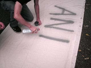"""Spray painting a message on a banner. This banner would ultimately read, """"ANTI-CAPITALISTA""""."""