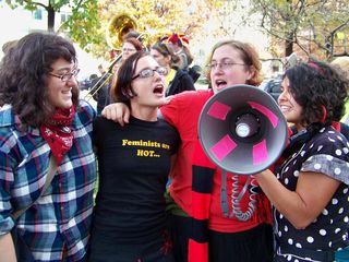 Radical cheerleaders sing a song into the bullhorn.