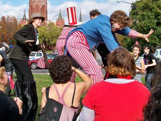 """Arriving in the park at the center of Thomas Circle, the people on the stilts, whose costumes were designed to somewhat represent capitalism, made their grand finale. Here, with """"encouragement"""" from the anti-capitalist crowd gathered, the folks on stilts lost their balance and made a dramatic fall to the ground."""