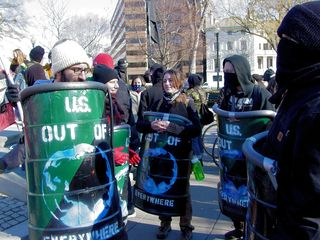 """These shields, which read """"U.S. OUT OF EVERYWHERE"""", were made of 90-degree sections of a plastic barrel. They were painted with the green-and-black flag of green anarchism as a background, overlaid with a picture of the Earth showing the eastern hemisphere and the lettering. Then they had padding added to the top, and a neck strap. These shields often held the front spot in the march."""