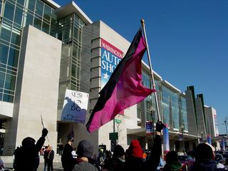 Our black bloc passes right by the main entrance to the Washington Convention Center, with flags flying and signs raised high.
