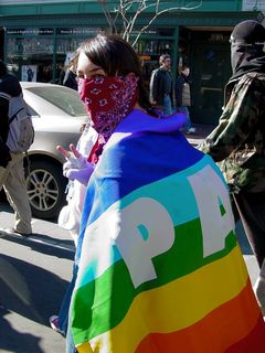 """This masked woman gives the peace sign while wrapping a rainbow """"PACE"""" (peace in Italian) flag."""