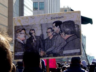 This sign shows an illustration depicting the meeting between Saddam Hussein and Donald Rumsfeld in December 1983.