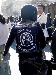 """This woman's jacket shows a stylized anarchy sign and the message """"Class war by all means necessary""""."""