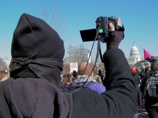 As the Capitol comes into view, a fellow black bloc participant takes video footage of the march.