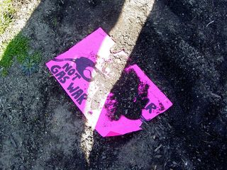 """On the ground, I found a discarded sign showing a gas pump and the words, """"Class war not gas war""""."""