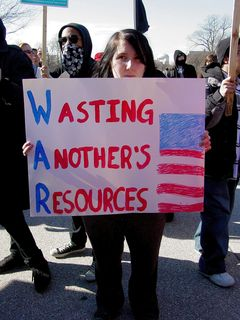 """This woman's sign turns the word """"war"""" into an acronym: Wasting Another's Resources."""