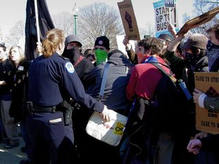 A Capitol Police officer is attempting to arrest a demonstrator. Note her hand on the person's bag. The remainder of the black bloc would not give him up without a fight. The officer ultimately gave up the fight.