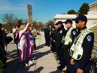 """A woman dressed in pink holds up a sign to a row of police officers. The sign says, """"Bring my husband home now!"""""""
