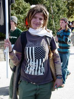 A woman holds a black flag while wearing another Anti-Flag shirt.