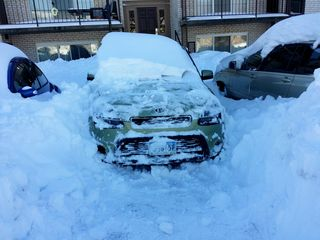 Clearing the snow from the front of the car, but still firmly stuck in place, as the wheels aren't free yet.