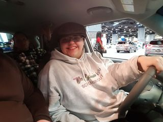 Elyse pretends to drive one of the new Souls, while Dave rides in the back seat.