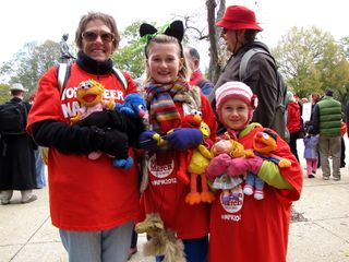 Some people held other representations of puppet characters, such as this family, which carried stuffed animals based on Sesame Street's puppet characters.