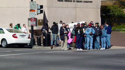 """Participants in the feeder march wait to cross the street at the opposite corner of 16th and Eye Streets, and then held up their """"Our dreams will never fit in their ballot boxes"""" banner for all to see while crossing."""