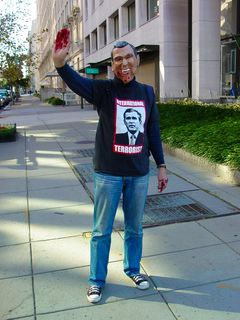 """A person waves while wearing a George W. Bush mask, and t-shirt featuring an image of George W. Bush and the words """"International Terrorist"""". The Bush mask had some of the teeth modified to look like fangs, and had fake blood below the mouth. Additionally, the person's hands were covered with fake blood. Reminds me of the """"Bloody Hands"""" sign shown at the anti-war procession on October 2."""