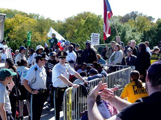 """Behind the speaker's area, all sorts of people, with some wearing union-related apparel, others wearing more activist-style clothing (note the yellow """"Free Mumia"""" shirt in the right-side photo), and some carrying flags, used the area as a sort of passageway from one side to the other. Park Police also kept an eye on the group on the steps from that location."""